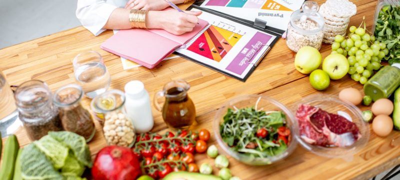 Writing a diet plan on the table full of healthy food