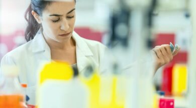 Concentrated chemist holding pipette at laboratory