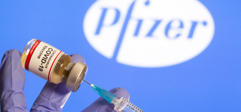 """FILE PHOTO: A woman holds a small bottle labeled with a """"Coronavirus COVID-19 Vaccine"""" sticker and a medical syringe in front of displayed Pfizer logo in this illustration"""