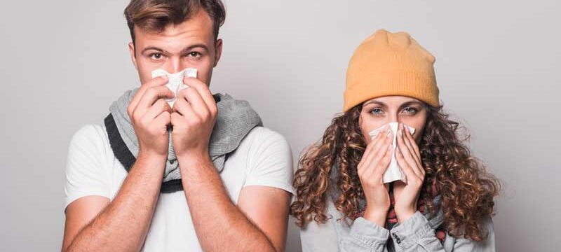 portrait-couple-blowing-their-nose-with-tissue-paper-gray-background