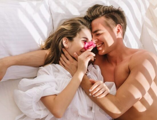 cheerful-young-couple-love-lying-white-bed-enjoying-honeymoon-sunny-morning-smiling-handsome-man-with-bronze-skin-embracing-his-magnificent-girlfriend-vintage-blouse-resting-pillows_197531-3184