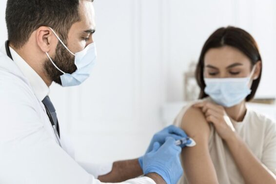 doctor-vaccinating-young-woman_23-2148755633