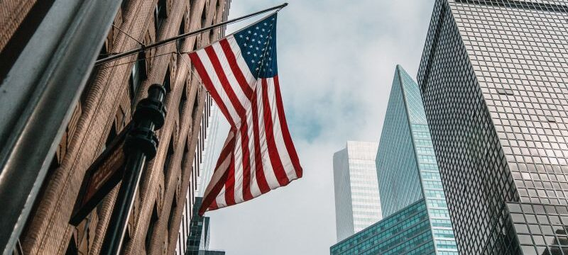 the USA or United States of America flag on a flagpole near skyscrapers under a cloudy sky