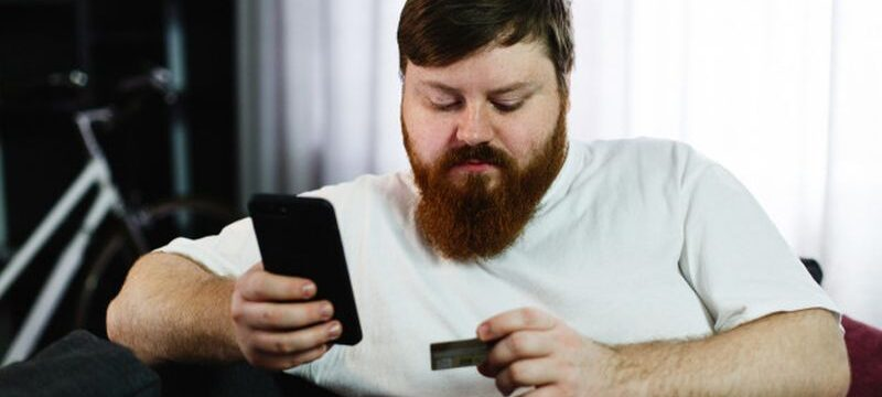 fat-man-types-number-credit-card-his-phone-sitting-couch_8353-5515
