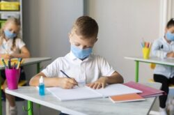 kids-writing-classroom-while-wearing-medical-masks_23-2148672255