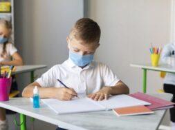 kids-writing-classroom-while-wearing-medical-masks_23-2148672255