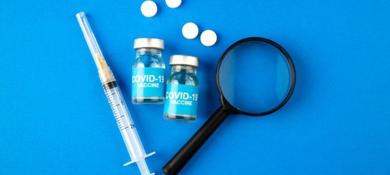 top-view-covid-vaccine-with-magnifier-injection-pills-blue-background-hospital-health-covid-lab-science-pandemic-virus-drug_179666-19746