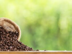 coffee-bean-sack-wooden-tabletop-against-grunge-green-blur-background_1323-255