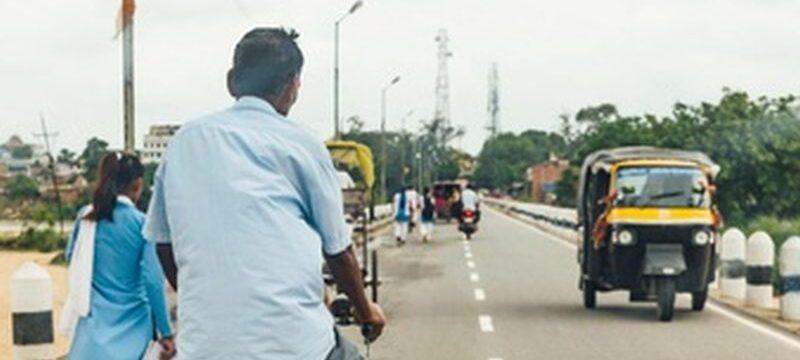 man-riding-bicycle-people-walking-road-with-cars-running-near-mahabodhi-temple-bodh-gaya-bihar-india_43263-2192