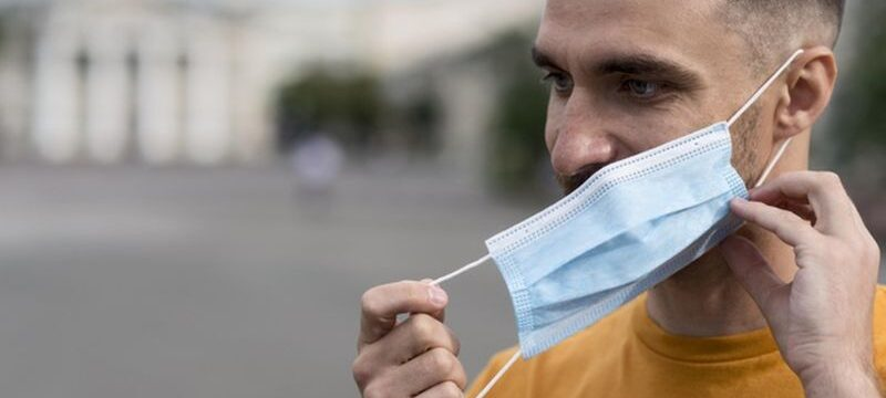 man-taking-off-his-medical-mask-outdoors_23-2148648198