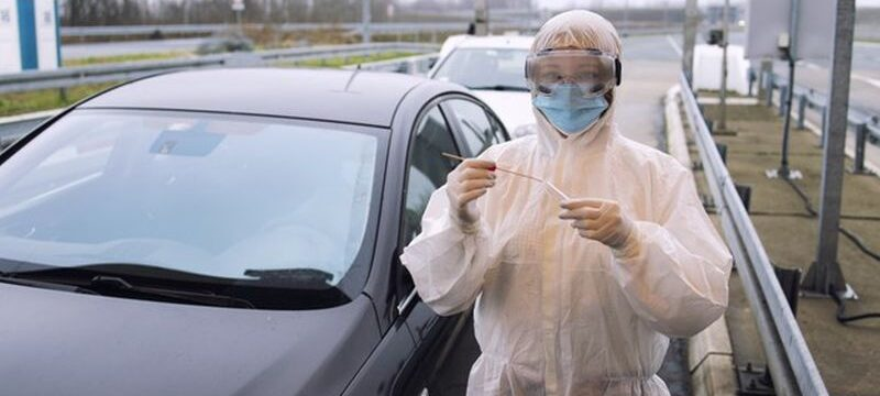 medical-heath-care-worker-protective-white-suit-standing-border-crossing-ready-test-passengers-corona-virus_308072-42