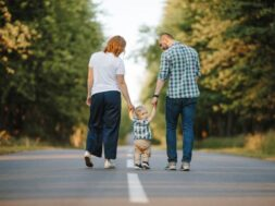 parents-holding-their-little-son-are-walking-road_8353-11372