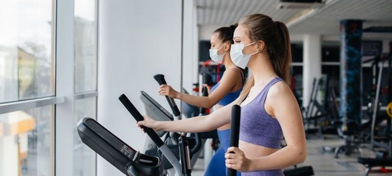 two-young-beautiful-girls-exercise-gym-wearing-masks-during-pandemic_180601-9453
