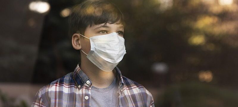 boy-with-face-mask-looking-outdoors-through-windows_23-2148806355