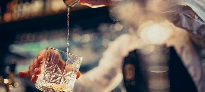 handsome-bartender-making-drinking-cocktails-counter_1303-19783