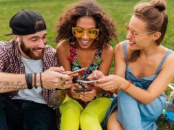happy-young-company-smiling-friends-sitting-park-using-smartphones-man-women-having-fun-together_285396-8722 (3)
