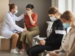 male-doctor-supporting-patient-while-she-crying-they-sitting-corridor-hospital-with-other-people_249974-5230