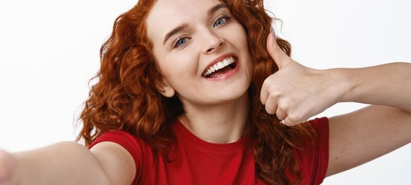 Selfie of young happy redhead girl with curly hairstyle showing thumb up, praise and recommend something good, smiling at smartphone camera, white background