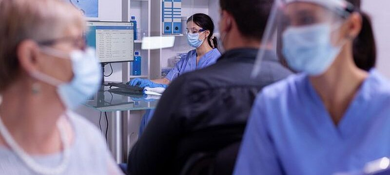 young-nurse-wearing-protection-mask-visor-against-coronavirus-infection-typing-computer-new-patients-appointments_482257-1264